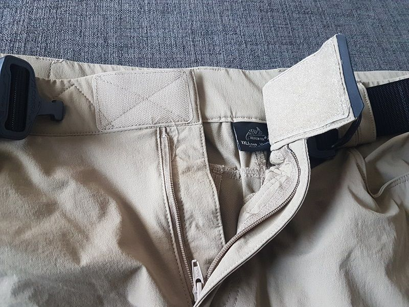 The elastic waist with a Velcro fastener is great to adjust the waist size even without a belt. Putting load in the pockets does not make the pants get any loose or slide down. The fastener locks the trousers on one's waist very securely and comfortably. The fly is YKK zippered.